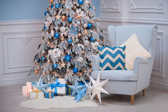 Christmas home interior - a cozy armchair and decorated fir in blue white colors Royalty Free Stock Photos