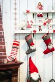 Fireplace and decorations on the mantelpiece. Christmas home interior decorations. Christmas socks for presents and decorations on white wooden wall Stock Image