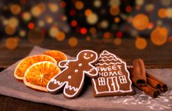 Christmas homemade gingerbread cookies on wooden table, slices of dry orange and colored lights on background royalty free stock images