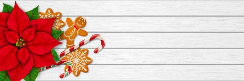 Christmas horizontal web banner with white wooden background. Horizontal Christmas web banner. Poinsettia, gingerbread cookies, candy canes and place for your Royalty Free Stock Photography