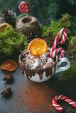 Christmas hot chocolate in a black cup with caramelized oranges, fir branches and candy cane on dark background, Selective focus Stock Images