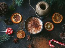 Christmas hot chocolate in a black cup with caramelized oranges, fir branches and candy cane on dark background, Selective focus Royalty Free Stock Images