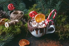 Christmas hot chocolate in a black cup with caramelized oranges, fir branches and candy cane on dark background, Selective focus. Christmas hot chocolate in a royalty free stock photo