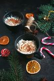 Christmas hot chocolate in a black cup with caramelized oranges, fir branches and candy cane on dark background, Selective focus Royalty Free Stock Photo