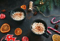 Christmas hot chocolate in a black cup with caramelized oranges, fir branches and candy cane on dark background, Selective focus Stock Photos