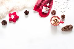 Christmas hot chocolate with marshmallow, cone, white fur, red felt star, knitted socks on white background. Flat lay. Christmas holiday composition. Hot Royalty Free Stock Photography