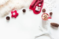 Christmas hot chocolate with marshmallow, cone, white fur, red felt star, knitted socks on white background. Winter. Christmas holiday composition. Hot Stock Photos