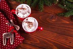 Christmas hot chocolate with marshmelow on a dark wooden background, christmas tree branches decorating. Stock Photography