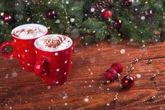 Christmas hot chocolate with marshmelow on a dark wooden background, christmas tree branches decorating. Stock Photo