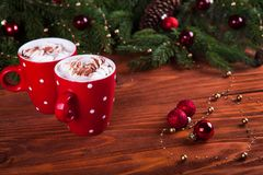 Christmas hot chocolate with marshmelow on a dark wooden background, christmas tree branches decorating. Stock Image