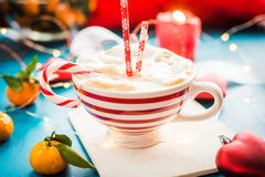 Christmas hot chocolate with marshmelow, christmas lights. Christmas hot chocolate with marshmelow on a dark wooden background, christmas tree branches stock photo