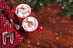 Christmas hot chocolate with marshmelow on a dark wooden background, christmas tree branches decorating. Royalty Free Stock Photo