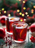 Christmas hot cranberry tea, orange pomegranate punch or mulled wine in a rustic wooden table. Closeup. Stock Photo