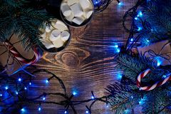 Christmas hot drink. Cocoa with marshmallow, garland and spruce branches on a wooden background. Top view Stock Images