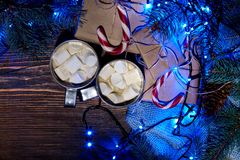 Christmas hot drink. Cocoa with marshmallow, garland and spruce branches on a wooden background. Top view Stock Photography
