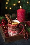Christmas hot drink. Christmas hot tea with lemon and cinnamon at the table with christmas decoration stock image