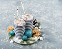 Christmas hot drinks with marshmellows. Two mugs of sweet cacao loaded with marshmellows and some cookies Royalty Free Stock Image