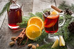 Christmas hot mulled wine with cinnamon, orange and christmas tree on wooden board. Winter tradition drink. Close up Royalty Free Stock Photography