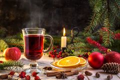 Image with mulled wine. Christmas hot mulled wine with cinnamon, orange and spruce with a candle on a dark background Royalty Free Stock Photos