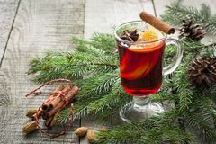 Christmas hot mulled wine with cinnamon, orange and christmas tree on board. Winter tradition drink. Christmas hot mulled wine with cinnamon, orange and Royalty Free Stock Image