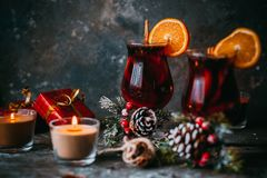 Christmas hot mulled wine. With spices, candle and traditional New Year decorations and orange on wooden background Stock Photo