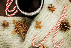 Christmas hot steaming cup of glint wine with spices, anise, cookies in a shape of star, red candies, fir cones, pepper and gray. Scarf on wooden background stock photos