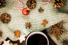 Christmas hot steaming cup of glint wine with spices, anise, cookies in a shape of star, red candies, pepper, fir cones and gray. Scarf on wooden background stock images