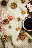 Christmas hot steaming cup of glint wine with spices, anise, cookies in a shape of star, red candies, pepper, fir cones and gray. Scarf on wooden background stock photography