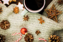 Christmas hot steaming cup of glint wine with spices, anise, cookies in a shape of star, red candies, pepper, fir cones and gray. Scarf on wooden background royalty free stock images