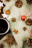 Christmas hot steaming cup of glint wine with spices, anise, cookies in a shape of star, red candies, pepper, fir cones and gray. Scarf on wooden background royalty free stock photos