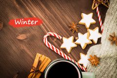 Christmas hot steaming cup of glint wine with spices, anise, cookies in a shape of star, red candies, pepper and gray scarf on. Wooden background with text stock photos
