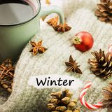 Christmas hot steaming cup of glint wine with spices, anise, cookies in a shape of star, red candies, pepper and gray scarf on. Wooden background with text stock photography