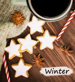 Christmas hot steaming cup of glint wine with spices, anise, cookies in a shape of star, red candies, pepper and gray scarf on. Wooden background with text royalty free stock photos