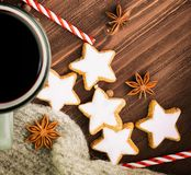 Christmas hot steaming cup of glint wine with spices, anise, cookies in a shape of star, red candies, pepper and gray scarf on. Wooden background. Copy space royalty free stock photos