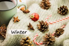 Christmas hot steaming cup of glint wine with spices, anise, cookies in a shape of star, red candies, pepper and gray scarf on. Wooden background with text royalty free stock photo