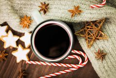 Christmas hot steaming cup of glint wine with spices, anise, cookies in a shape of star, red candies, pepper and gray scarf on. Wooden background. View from stock images