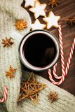 Christmas hot steaming cup of glint wine with spices, anise, cookies in a shape of star, red candies, pepper and gray scarf on. Wooden background. View from stock photography