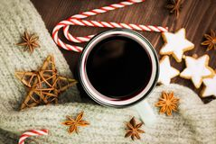 Christmas hot steaming cup of glint wine with spices, anise, cookies in a shape of star, red candies, pepper and gray scarf on. Wooden background. View from royalty free stock photo