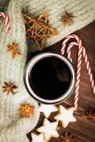 Christmas hot steaming cup of glint wine with spices, anise, cookies in a shape of star, red candies, pepper and gray scarf on. Wooden background. View from royalty free stock images
