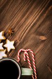 Christmas hot steaming cup of glint wine with spices, anise, cookies in a shape of star, red candies, pepper on wooden background. Copy space for text. View royalty free stock photo