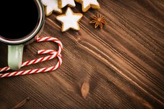 Christmas hot steaming cup of glint wine with spices, anise, cookies in a shape of star, red candies, pepper on wooden background. Copy space for text. View royalty free stock images