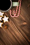 Christmas hot steaming cup of glint wine with spices, anise, cookies in a shape of star, red candies, pepper on wooden background. Copy space for text. View royalty free stock photos