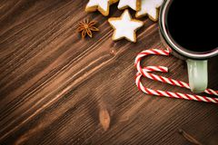 Christmas hot steaming cup of glint wine with spices, anise, cookies in a shape of star, red candies, pepper on wooden background. Copy space for text. View stock image