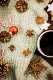 Christmas hot steaming cup of glint wine with spices, anise, fir cones, cookies in a shape of star, red candies, pepper and gray. Scarf on wooden background stock images