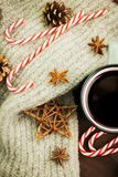 Christmas hot steaming cup of glint wine with spices, anise, fir cones, cookies in a shape of star, red candies, pepper and gray. Scarf on wooden background royalty free stock photography