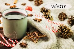 Christmas hot steaming cup of glint wine with spices, cinnamon, anise, cookies in a shape of star, red candies, fir cones, pepper. And gray scarf on wooden royalty free stock photos