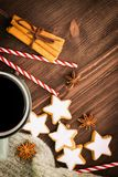 Christmas hot steaming cup of glint wine with spices, cinnamon, anise, cookies in a shape of star, red candies, pepper and gray. Scarf on wooden background royalty free stock photos