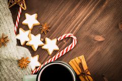 Christmas hot steaming cup of glint wine with spices, cinnamon, anise, cookies in a shape of star, red candies, pepper and gray. Scarf on wooden background stock image