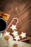 Christmas hot steaming cup of glint wine with spices, cinnamon, anise, cookies in a shape of star, red candies, pepper and gray. Scarf on wooden background royalty free stock images
