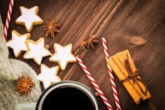 Christmas hot steaming cup of glint wine with spices, cinnamon, anise, cookies in a shape of star, red candies, pepper and gray. Scarf on wooden background royalty free stock image